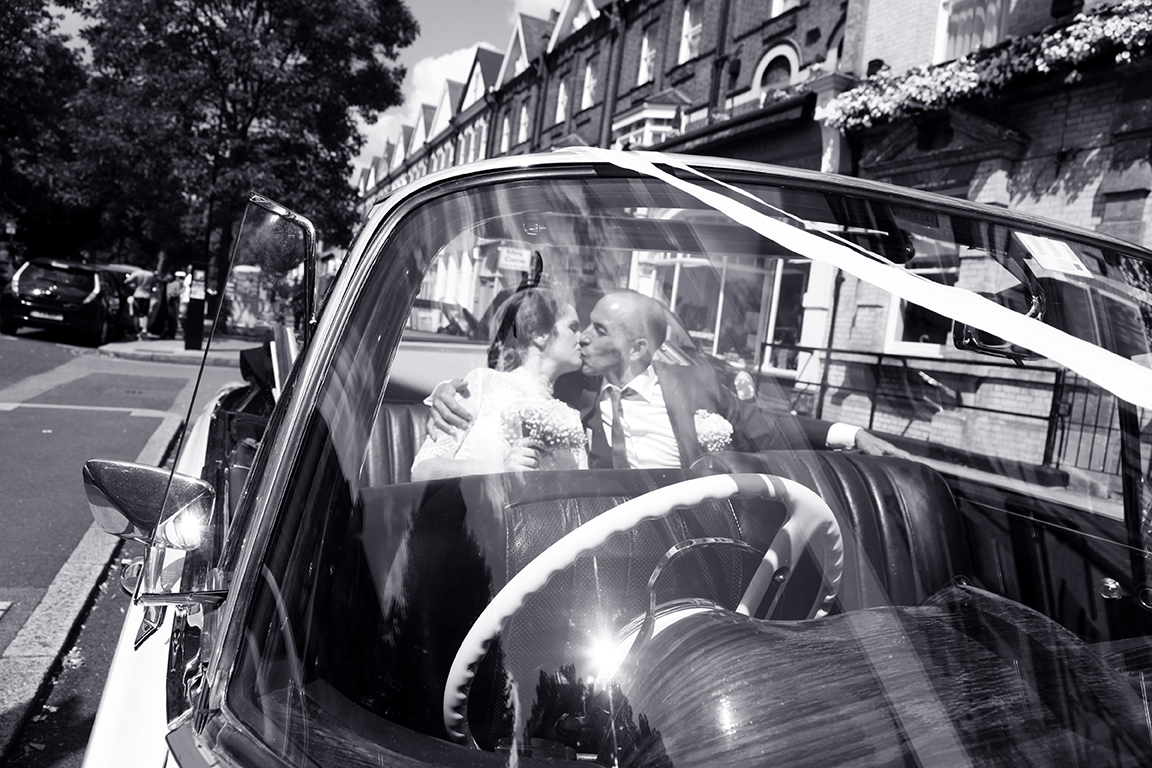 Bride and grom in wedding car outside Drayton Court Hotel.