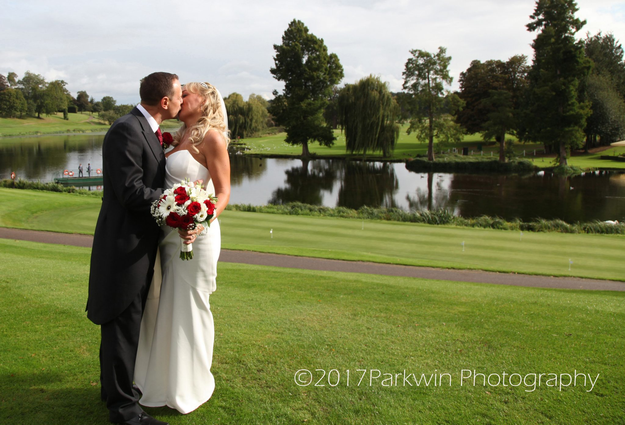 Bride and groom by lake at Brocket Hall