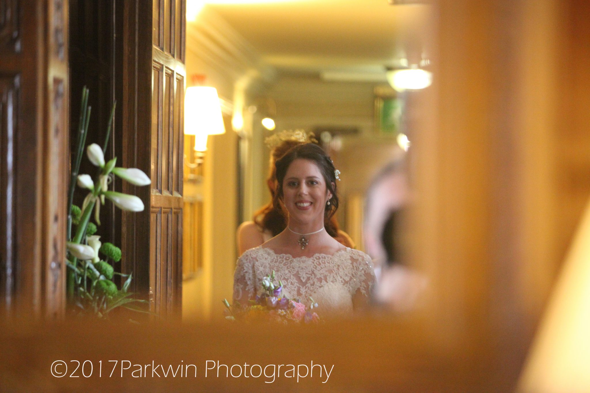 bride looking into mirror as she walks to wedding ceremony room Hanbury Manor